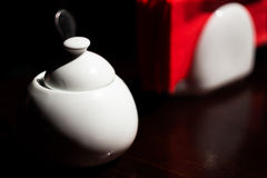 White sugar bowl and red napkins on dark wooden table Stock Photo