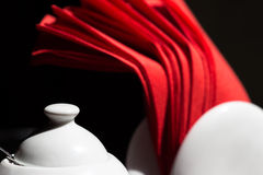 White sugar bowl and red napkins isolated on black background Royalty Free Stock Images
