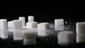 White Sugar Cane Cubes Glucose Sweetener Slowmo. Sugar is made from sugar cane and is used as a sweetener ingredient in food products and drinks. Some consider stock video footage