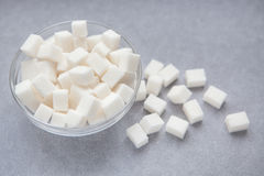 White sugar cubes on gray background. White sugar cubes in glass on gray background Stock Images