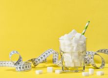 White sugar cubes measuring tape Weight control diet detox. Glass with white sugar cubes and measuring tape. Weight control, diet and detox concept Royalty Free Stock Image