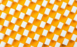White sugar cubes on orange background. Flat lay Royalty Free Stock Images