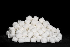 White sugar cubes. Stacked on a black background Royalty Free Stock Images