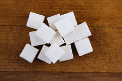 Sugar cubes on a wooden cutting board Royalty Free Stock Photos