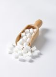 White sugar cubes. In wooden scoop Stock Images