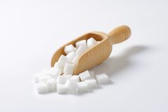 White sugar cubes. In wooden scoop Royalty Free Stock Photo