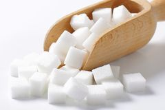 White sugar cubes. In wooden scoop Royalty Free Stock Photos