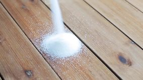 White sugar pouring into heap on wooden table. Food, junk-food, cooking and unhealthy eating concept - white sugar pouring into heap on wooden table stock video