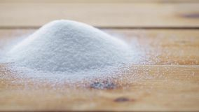 White sugar pouring into heap on wooden table stock footage