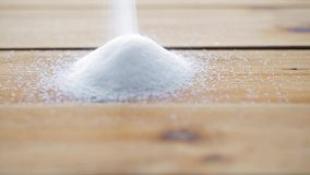 White sugar pouring into heap on wooden table. Food, junk-food, cooking and unhealthy eating concept - white sugar pouring into heap on wooden table stock video footage