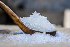 White sugar in wooden scoop.Sugar is the generic name for sweet, soluble Stock Image