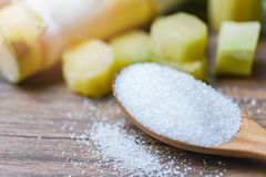 White sugar on wooden spoon and sugar cane wood table background. White sugar on wooden spoon and sugar cane on wood table background stock photo