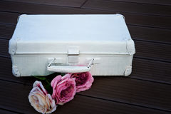 White suitcase with pink flowers against a dark floor. Stock Photos
