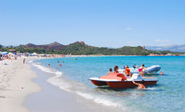 White summer beach with blue sea, people, boat and pedal Royalty Free Stock Photos
