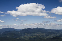 White summer clouds overt the mountains Stock Photos