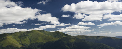 White summer clouds overt the mountains Stock Photography