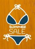White summer sale text and blue bikini against wood. Digital composite of White summer sale text and blue bikini against wood Royalty Free Stock Photo