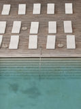 White sun-loungers and deckchairs next to the swimming pool with crystal blue water Stock Photo