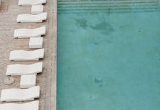 White sun-loungers and deckchairs next to the swimming pool with crystal blue water Royalty Free Stock Images