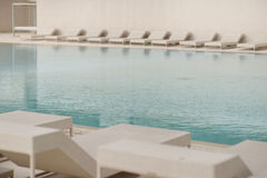 White sun-loungers and deckchairs next to the swimming pool with crystal blue water Royalty Free Stock Photos