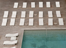 White sun-loungers and deckchairs next to the swimming pool with crystal blue water Stock Photography