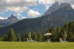 White Sun Loungers and Sun Umbrellas on Green Meadow in Italian Dolomites Alps Scenery.  royalty free stock photo