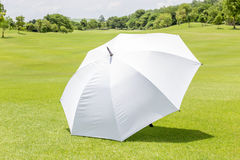 The white sun umbrella place on green grass golf course using for sun protection. stock image