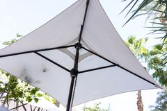 White sun umbrella for shade low angle view. White sun umbrella for shade low angle royalty free stock images