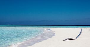 White sunbed near tropical calm beach with turquoise sea water and white sand. Maldives islands Stock Photo