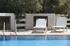 White sunbeds and swimming pool in summer Royalty Free Stock Image