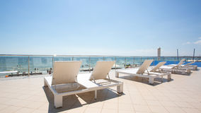 White sunbeds at the terrace of a hotel near the tropical beach. A lot of white deck chairs near the sea beach. Summertime. Stock Image