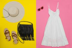 White sundress, black handbag, brown shoes and sunglasses. Brigh. T pink and yellow background Stock Photography