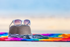 Sunglasses and beach hat on the beach. White sunglasses and beach hat on tropical beach stock image