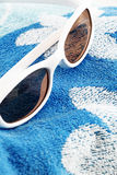 White sunglasses on a beach towel Stock Images