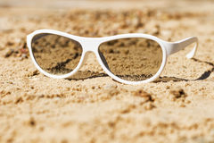 White sunglasses on the sand. The concept for the design of the holiday, summer Stock Photo