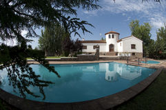 White sunny spanish villa. Large white sunny spanish villa with beautiful green garden with lovely swimming pool in the foreground and deep blue sky Royalty Free Stock Photos