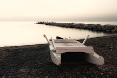 White sunset. A solitary boat on the beach at the sunset Stock Image