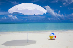 White sunshade and ball at the beach Royalty Free Stock Photo