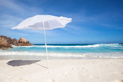 White sunshade and granit rocks at the beach Stock Photography