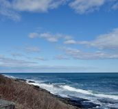 White surf coming in on Rocky Atlantic Shore. Low waves advancing toward black rocks at shore of Atlantic in Maine New England rocky coast under a blue sky with Stock Image