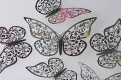 On the white surface lie decorations made of butterflies cut from foil. Royalty Free Stock Photos