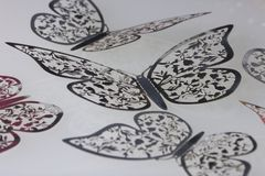 On the white surface lie decorations made of butterflies cut from foil. Royalty Free Stock Photography