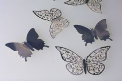 On the white surface lie decorations made of butterflies cut from foil. On the white surface lie decorations made of butterflies cut from foil Stock Images