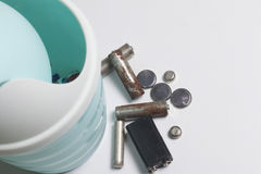 On the white surface is a plastic garbage can. Next to it lie the used batteries. Stock Images