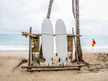 White surfboard abandoned on an empty sandy beach with waves in distance. stock images