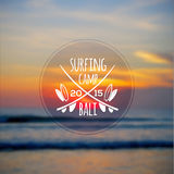 White surfing camp logo on blurred ocean sunset Royalty Free Stock Photos