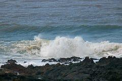 White surf breaking behind black rocks. Stock Image