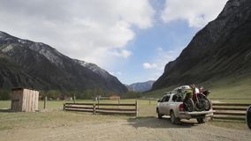 The white suv car with bicycles in pickup box arrives to the camping in the mountain valley.
