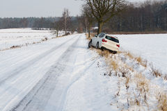 White SUV crashed in a country road kerbside. Due to slippery road covered in snow with skid marks Stock Image