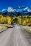 White SUV drivews down Country Road 12 out of Ridgway Colorado towards San Juan Mountains with Autumn Color stock photos